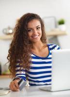 lächelnde Frau Online-Shopping mit Computer und Kreditkarte in foto