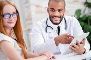 fröhlicher Arzt, der eine Tablette in seinen Händen hält und schaut foto