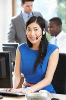 Geschäftsfrau, die Headset trägt, das im beschäftigten Büro arbeitet