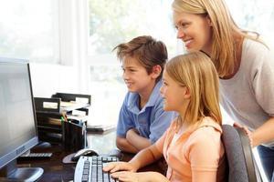 Mutter und Kinder benutzen den Computer zu Hause foto