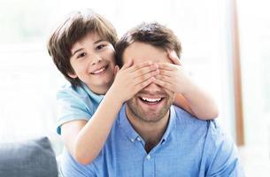 Junge, der Vaters Augen bedeckt foto
