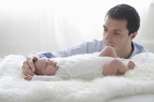 Vater streichelt den Kopf des Neugeborenen foto