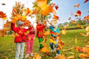 aktive Gruppe von Kindern spielt mit fliegenden Blättern foto