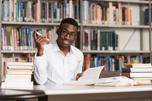 afrikanischer Mann, der in einer Bibliothek studiert foto