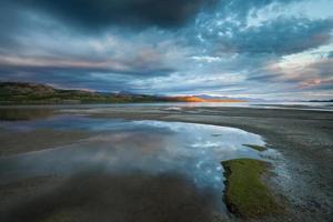 goldener Sonnenstrahl und dramatischer Himmel am See laberge