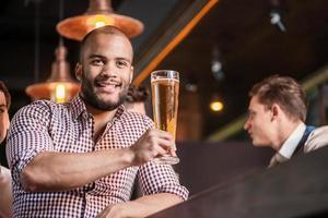 selbstbewusster Mann, der Bier an der Bar trinkt foto