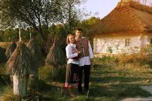 glückliches schönes Paar auf dem Hintergrund des traditionellen ukrainischen Hauses