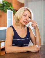traurige Frau, die auf Tisch sitzt