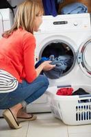 Frau lädt Kleidung in Waschmaschine foto