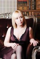 Porträt der traurigen Frau, die in einem Stuhl sitzt foto