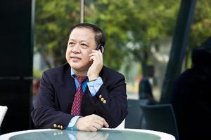 asiatischer Geschäftsmann, der auf Smartphone spricht