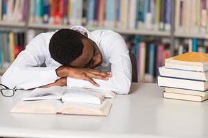 müder Student, der in der Bibliothek schläft foto