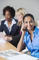 Geschäftsfrau auf Abruf mit Kollegen im Büro foto