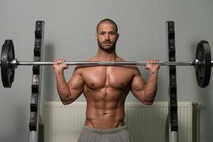 männlicher Bodybuilder, der schweres Gewicht für Schultern ausübt foto