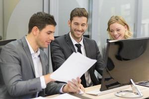 Gruppe von Geschäftsleuten in einer Besprechung, die am Computer arbeitet foto