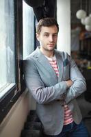 Hipster-Mann in modernen Bürohänden auf seiner Brust gekreuzt foto
