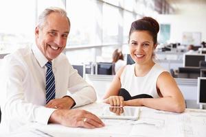 zwei Mitarbeiter im Büro eines Architekten, die vor der Kamera lächeln foto