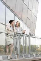 Volle Länge der jungen Geschäftsfrauen, die sich am Bürobalkon unterhalten foto