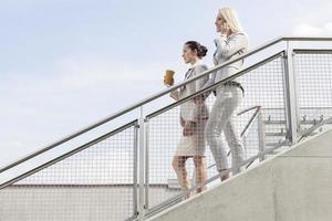 Profilaufnahme von Geschäftsfrauen, die Treppe gegen Himmel hinunter bewegen foto