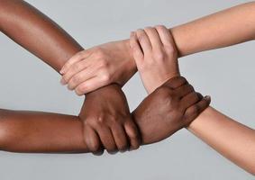 weiße kaukasische weibliche und schwarze afroamerikanische Hände, die zusammenhalten foto