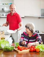 glücklicher älterer Mann und reife Frau, die Hausarbeit tun foto