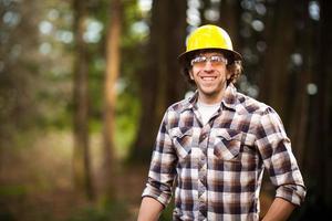 Mann Holzfäller im Wald mit Sicherheitsausrüstung foto
