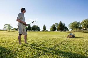 älterer Mann, der Gras mit Schere schneidet foto
