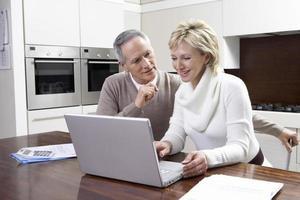 Paar, das Hausfinanzen auf Laptop berechnet foto
