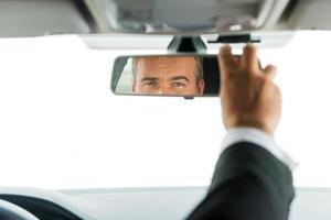 Mann, der Autospiegel einstellt. foto