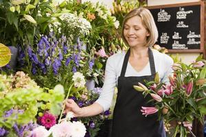 Frau arbeitet am Blumenladen lächelnd foto