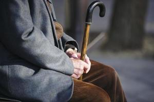 älterer Mann mit einem Stock, der auf Holzbank sitzt foto
