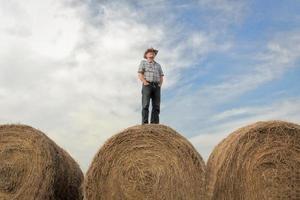 Mann, der auf riesigem Heuballen unter einem Sommerhimmel steht foto