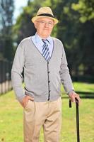 älterer Herr mit einem Stock, der im Park aufwirft foto