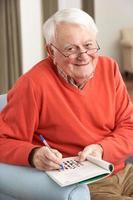 älterer Mann, der im Stuhl zu Hause entspannt Kreuzworträtsel vervollständigt