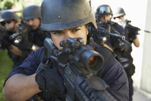 Gruppe von Polizisten, die mit Waffen zielen foto
