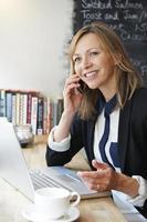 Geschäftsfrau, die auf dem Handy im Café spricht foto
