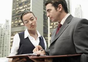 Geschäftsmann, der Papierkram zur Frau im Freien zeigt foto