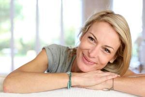 Porträt der blonden Frau, die auf Couch liegt foto