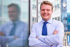 lächelnder Geschäftsmann, der außerhalb eines Gebäudes steht