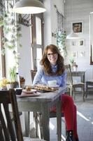 schöne Frau, die am Schreibtisch im Café sitzt foto