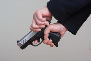Frau spannt eine Handfeuerwaffe