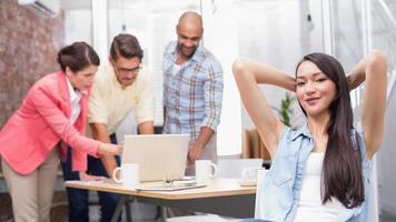 Frau mit den Händen hinter dem Kopf, während sein Kollege arbeitet foto