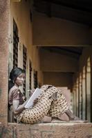 afrikanisches Bildungssymbol: schwarze Frau, die Notizen Hausaufgabenarbeitsbuch schreibt foto