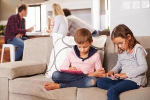 Kinder spielen mit neuer Technologie, während Erwachsene unterhalten foto