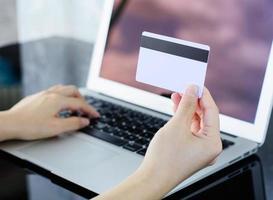 Frau, die Kreditkarte hält und Informationen in einen Laptop eingibt foto