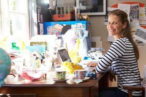 Frau, die kleines Geschäft vom Hauptbüro führt foto