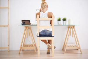 blonde Frau mit ihrem Laptop. Blick von hinten