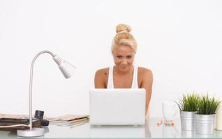 glückliches blondes Mädchen an ihrem Arbeitsbereich. Frontansicht