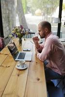 junger Student, der Informationen von einem Computer liest, der im Café sitzt foto