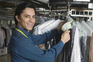 Besitzer prüft Kleideranhänger in der Wäsche foto